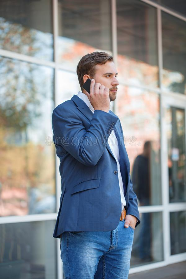En man i ett omslag står på gatan och talar på telefonen royaltyfri bild