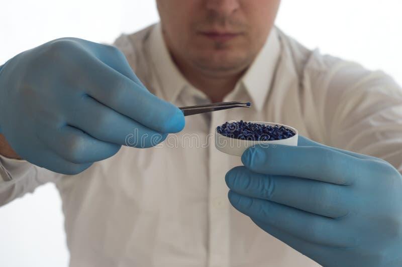 En man i ett vitt lag som rymmer pincett och plast- kulor, och partiklar i laboratoriumet royaltyfri fotografi