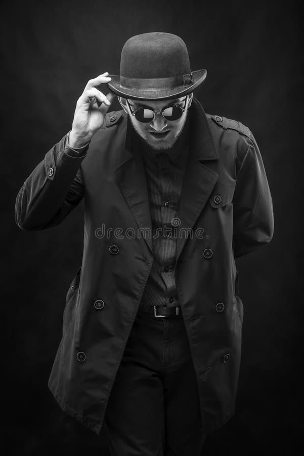 En man i exponeringsglas korrigerar hans hatt, en svartvit ram fotografering för bildbyråer