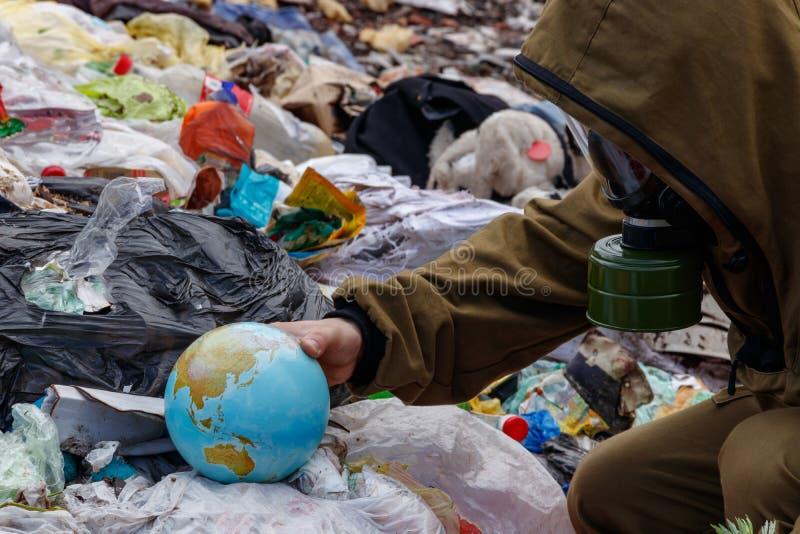 En man i en gasmask grundar ett jordklot i förrådsplatsen Folket förstör planetjorden Världen är mired i plast- skräp mot som kro fotografering för bildbyråer