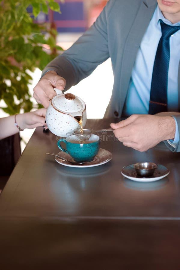 En man i en grått affärsdräkt och band sitter på tabellen och det hällande teet från bryggaren arkivfoton