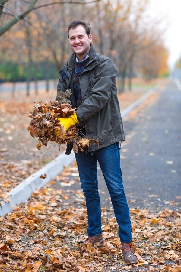 En man i gula rubber handskar tar bort de stupade sidorna för hösten, i parkera arkivfoton