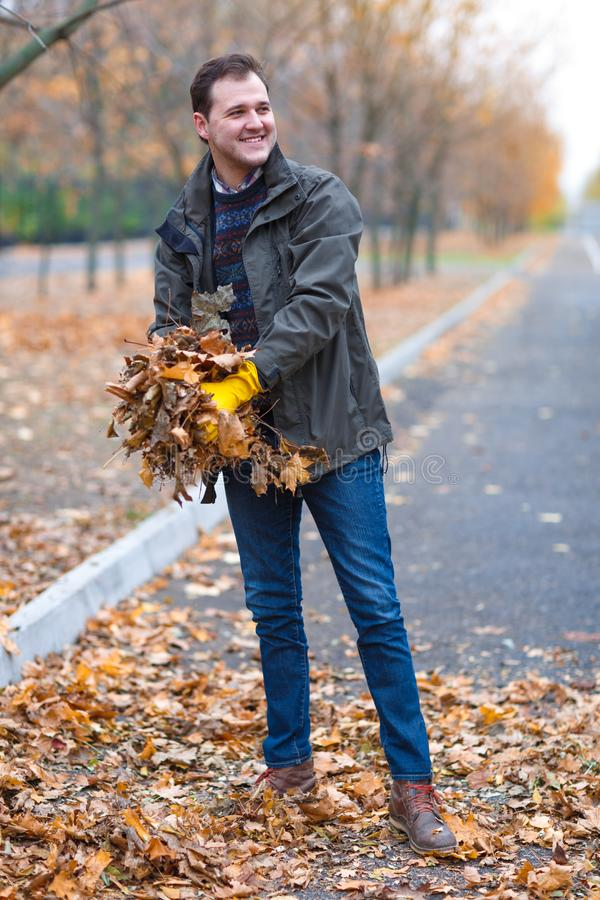 En man i gula rubber handskar tar bort de stupade sidorna för hösten, i parkera arkivfoto