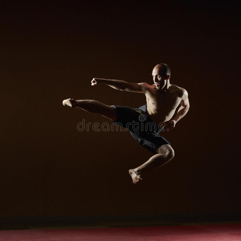 En man i en höjdhopp slår en spark fotografering för bildbyråer