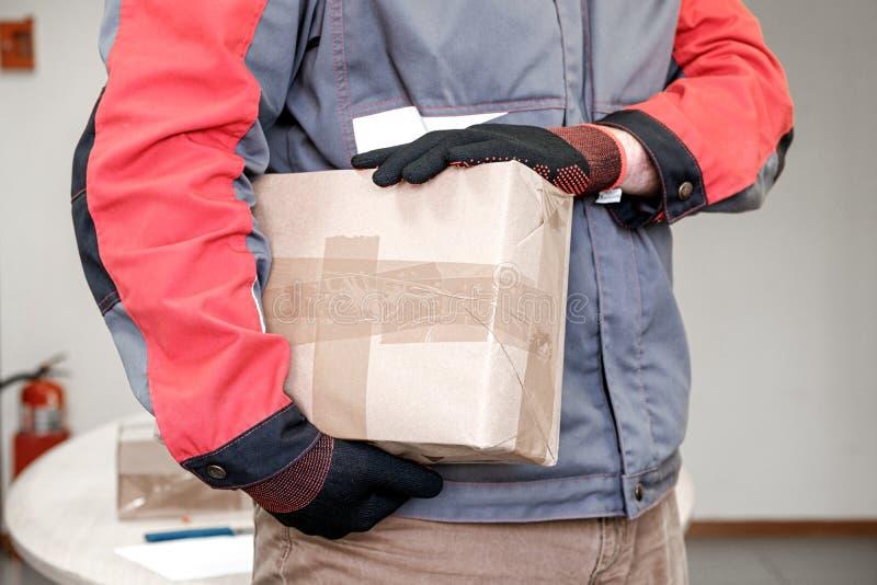 En man i handskar har ett paket som är förseglat för leverans arkivbild