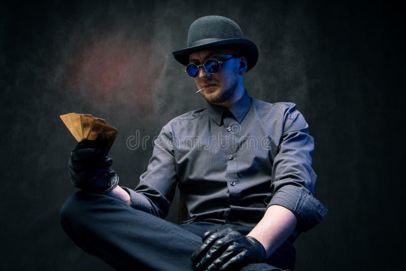 En man i handskar och svartexponeringsglas spelar kort i dobbleri arkivbilder