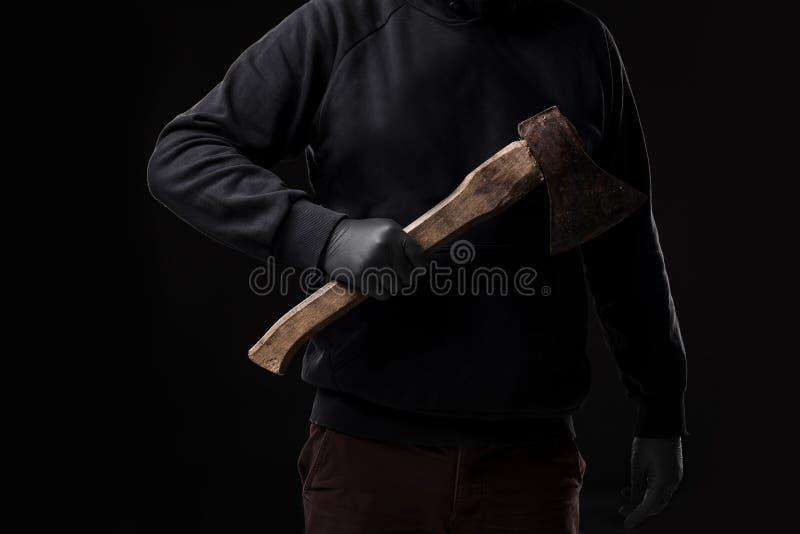 En man i handskar rymmer en yxa i hans händer mot en svart bakgrund royaltyfri fotografi