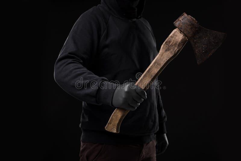 En man i handskar rymmer en yxa i hans händer mot en svart bakgrund royaltyfri bild