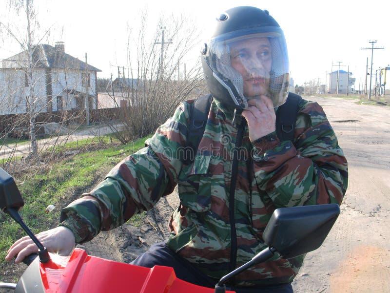 en man i en hjälm sitter på en röd motorcykel royaltyfri fotografi