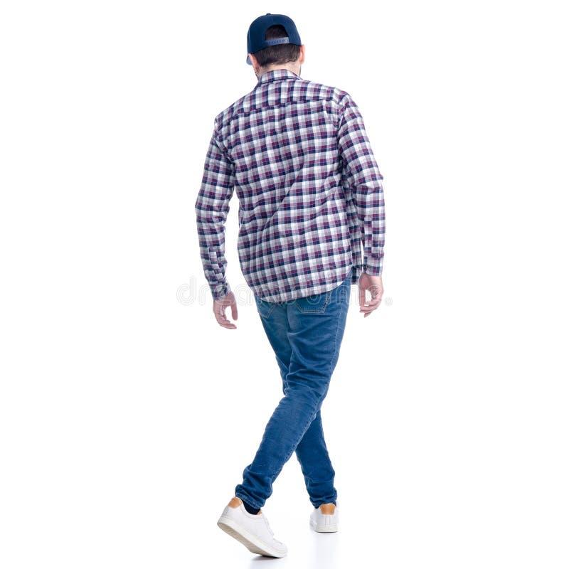 En man i jeans, skjorta och lock går att gå royaltyfria bilder