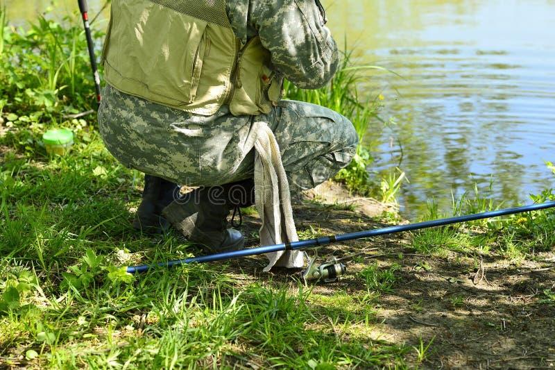 En man i kamouflagemetspö på flodbanken i försommar royaltyfria bilder