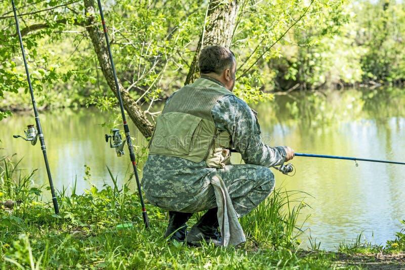 En man i kamouflagemetspö på flodbanken i försommar arkivbild