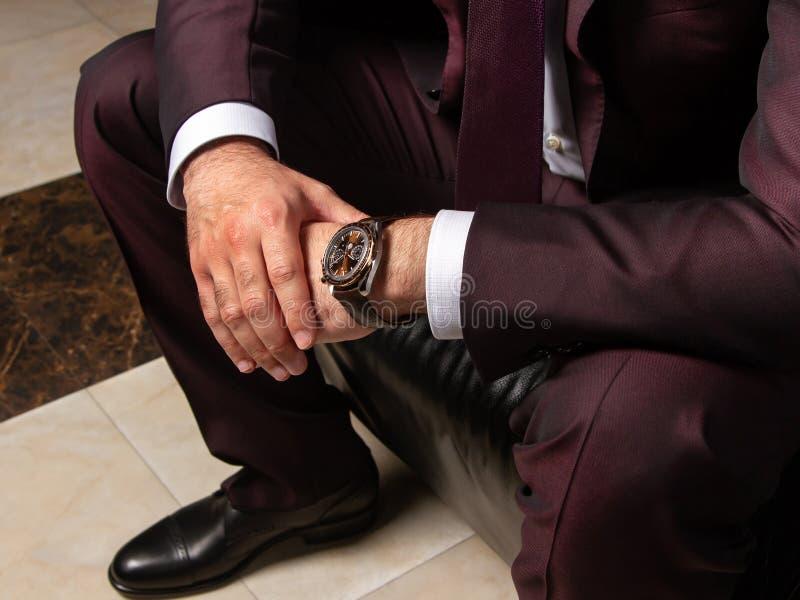 En man i en klassisk dräkt sitter på en svart lädersoffa, slut upp, rätsidan, bästa sikt royaltyfri foto