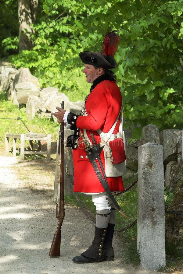 En man i likformig av en brittisk soldat av det revolutionära kriget i nationellt historiskt för minutman parkerar royaltyfria foton