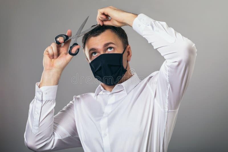 En man i en mask försöker självständigt tillhandahålla frisörtjänster när han befinner sig i karantän i hemmet arkivbild