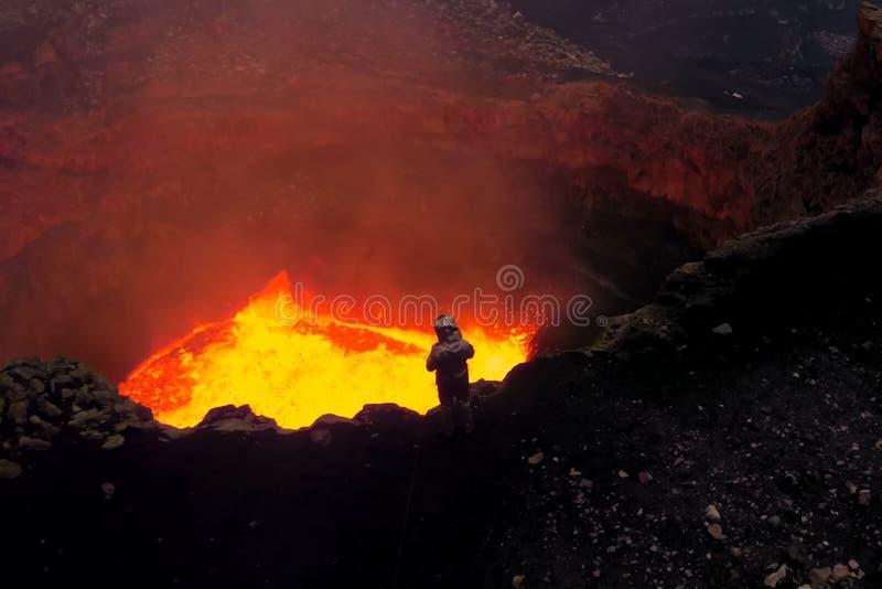 En man i en near mun för skyddande dräkt av vulkan med magma Smält magma i tysta ned arkivfoto