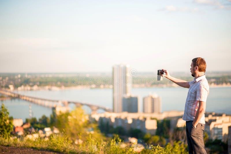 En man i en skjorta och byxa tar bilder av honom och naturen på telefonen Stående av en man i bakgrunden av Saratov, R royaltyfria bilder