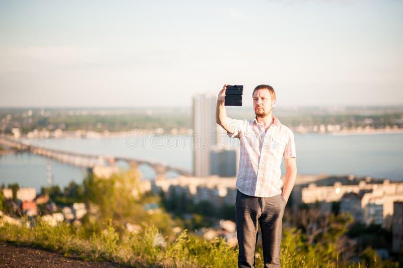En man i en skjorta och byxa tar bilder av honom och naturen på telefonen Stående av en man i bakgrunden av Saratov, R royaltyfri bild