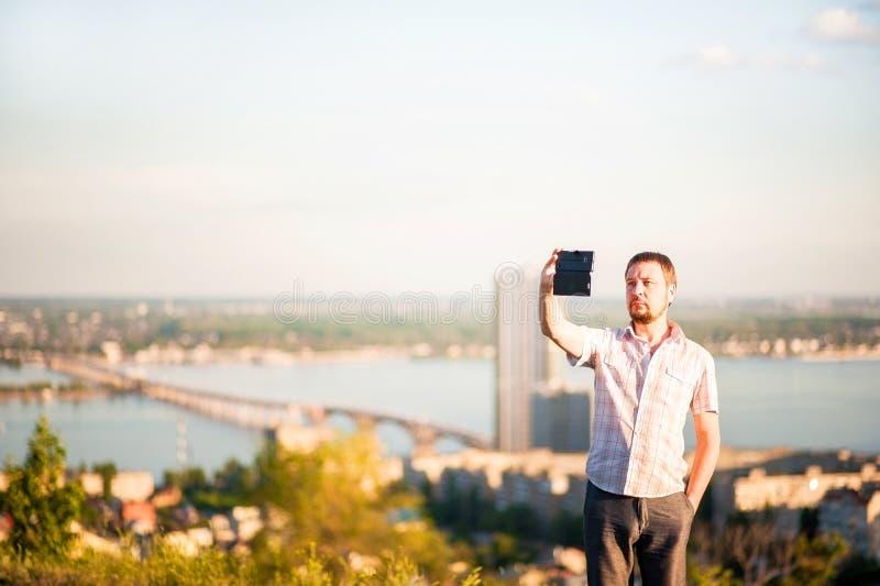 En man i en skjorta och byxa tar bilder av honom och naturen på telefonen Stående av en man i bakgrunden av Saratov, R arkivfoto