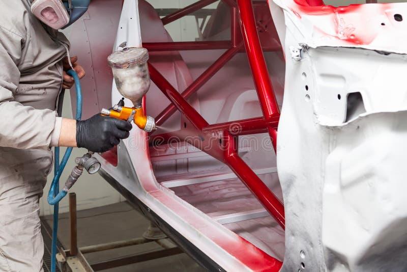 En man i skyddande overaller och en maskering rymmer en sprejflaska i hans hand och besprutar röd målarfärg på ramen av bilkroppe arkivbild