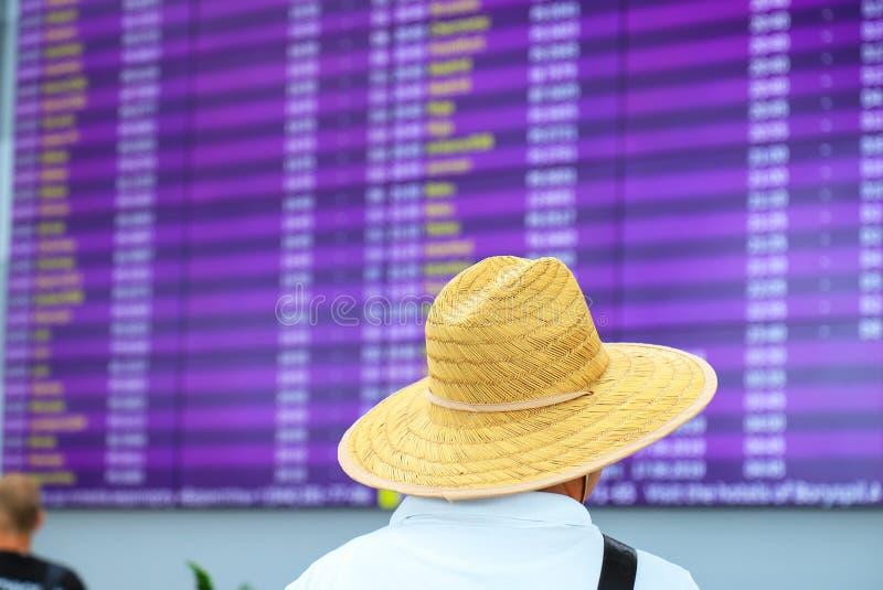 En man i en sugrörhatt står nära ett suddigt informationsbräde för ankomster och avvikelser Informationsställning på royaltyfri fotografi