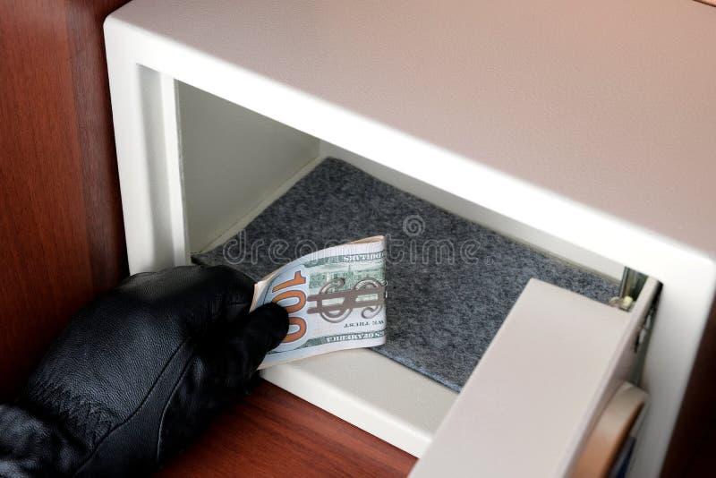 En man i en svart handske stjäler en bunt av amerikanska dollar Öppna ett bankkassaskåp med ett kombinationslås Brottsligt begrep royaltyfri bild