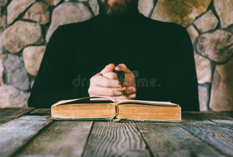 En man i svart kläder med pärlor för en bön i hand som ber av ett gammalt, öppnar framme boken arkivfoton