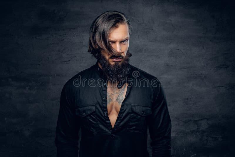 En man i svart skjorta med tatueringen på hans bröstkorg arkivbilder