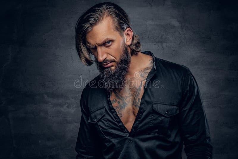 En man i svart skjorta med tatueringen på hans bröstkorg royaltyfria bilder