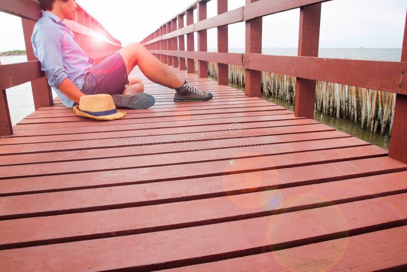 En man i tillfälliga kläder som bara sitter på träbron arkivfoto