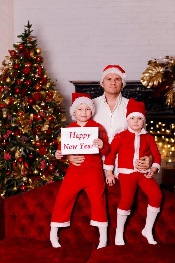 En man i en vit skjorta med två barn i röd dräkt royaltyfri bild