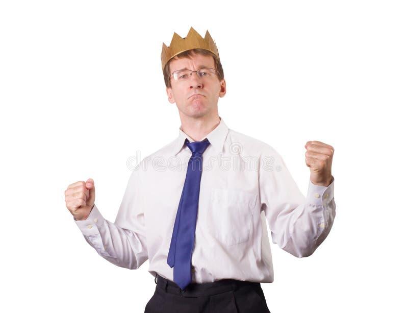 En man i en vit skjorta och band med en krona på hans huvud som behas med angelägenheterna Allt är bra i affär isolerat arkivfoto