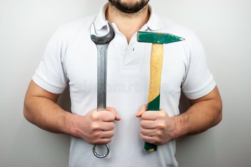 En man i en vit t-skjorta med en hammare och en skiftnyckel royaltyfri foto