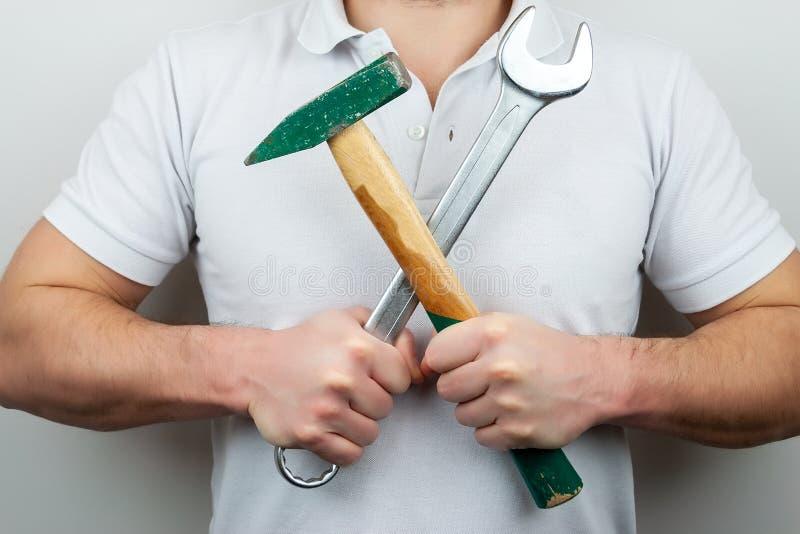 En man i en vit t-skjorta med en hammare och en skiftnyckel som på tvären rymmer dem royaltyfria bilder