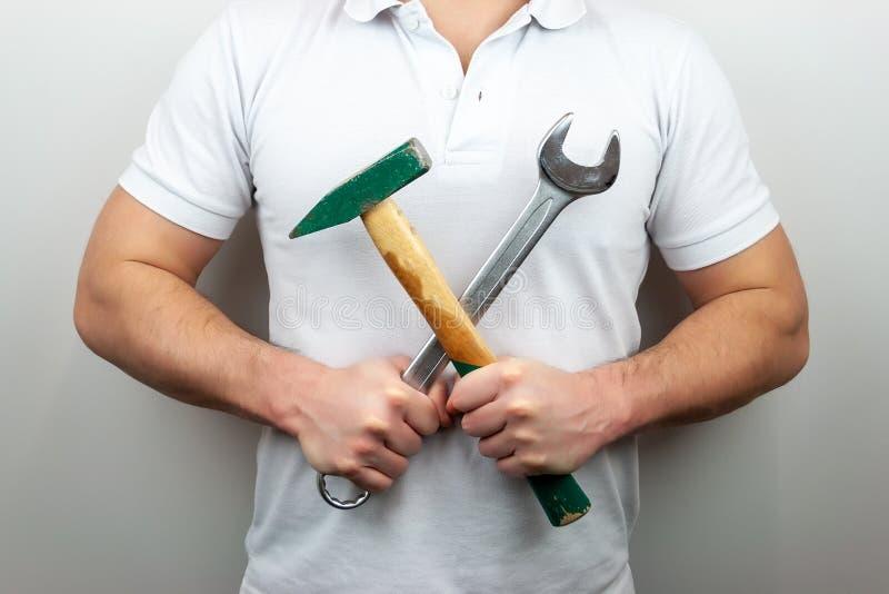 En man i en vit t-skjorta med en hammare och en skiftnyckel som p? tv?ren rymmer dem royaltyfria foton
