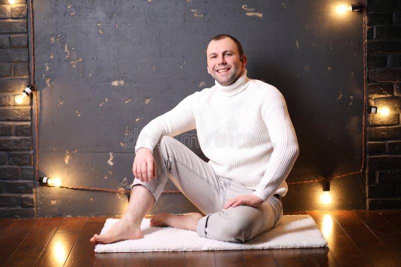 En man i en vit tröja lyssnar till musik royaltyfri foto