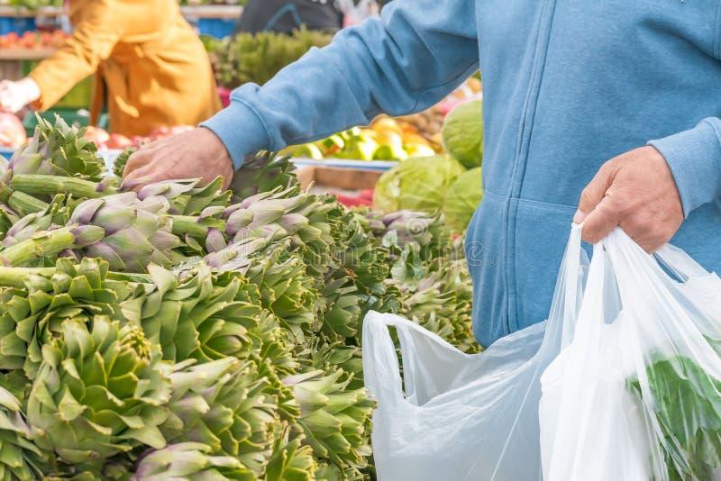 En man köper nya organiska grönsakkronärtskockor från lokala bönder i stadsmarknaden royaltyfri bild