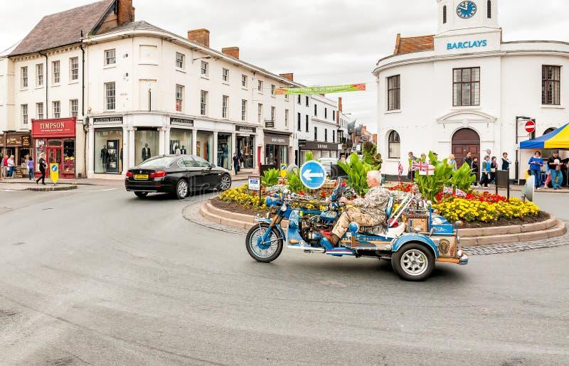 En man kör hans Harley Davidson moped till och med mitten av Stratford Upon Avon royaltyfri fotografi