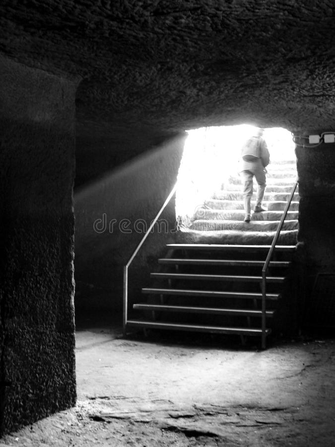 En man klättrar källaretrappan som är hög i solljuset i svartvitt fotografering för bildbyråer