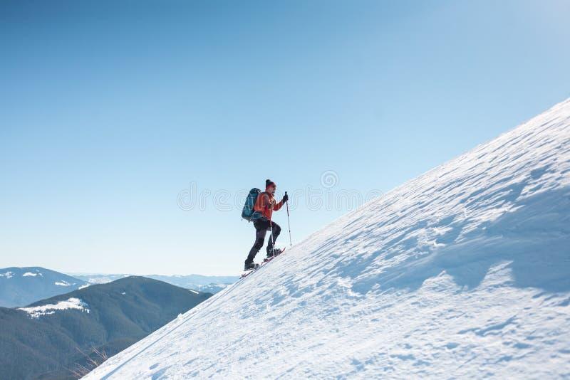 En man klättrar till överkanten av berget royaltyfria foton