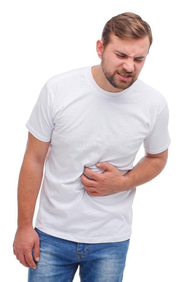 En man klamra sig fast intill hans mage och vrider hans framsida Isolerat över vitbakgrund arkivfoton