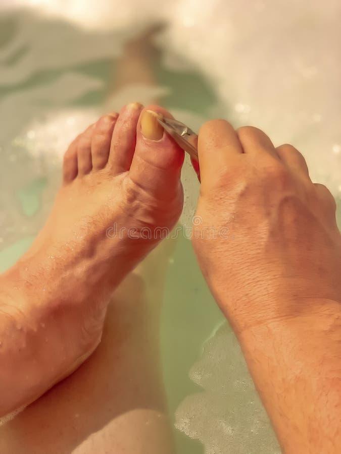En man klipper hans tånaglar royaltyfri bild