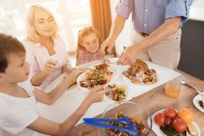 En man lägger ut en bakad kalkon till hans släktingar, som sitter på den festliga tabellen för tacksägelse arkivfoton