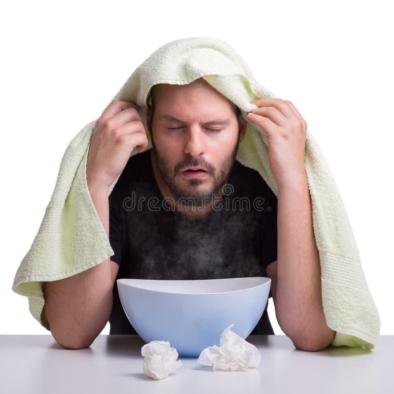 En man lider från influensan och inhalerar ånga för att få sunt isolerat på vit bakgrund royaltyfria bilder