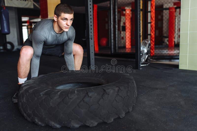 En man lyfter ett stort rullar in idrottshallen som utbildar för muskelmass arkivbild