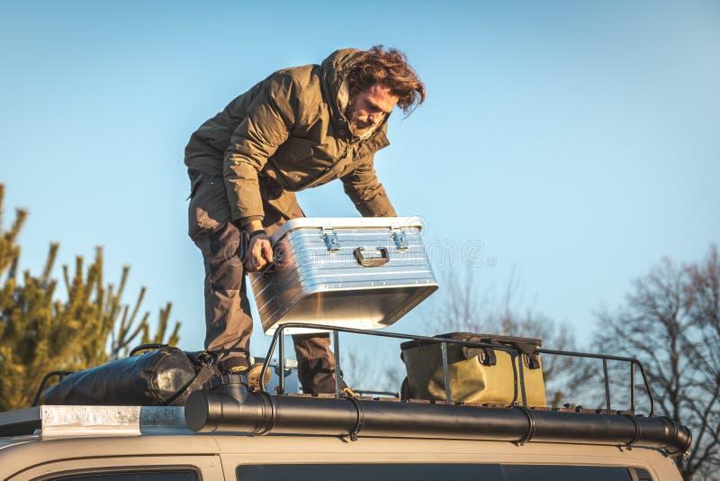 En man lyfter en metallask på taket av en campareskåpbil som av naturen omges royaltyfria foton