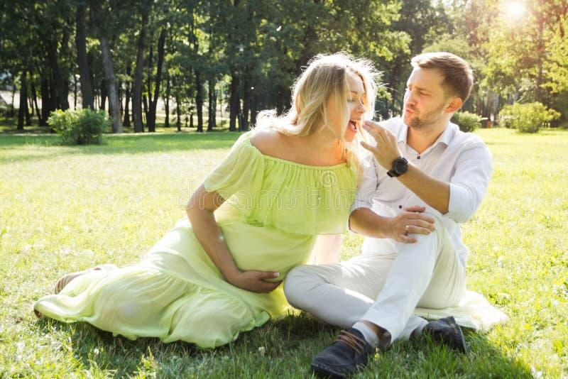 En man matar godis till sin gravida fru på en picknick i parken royaltyfria bilder