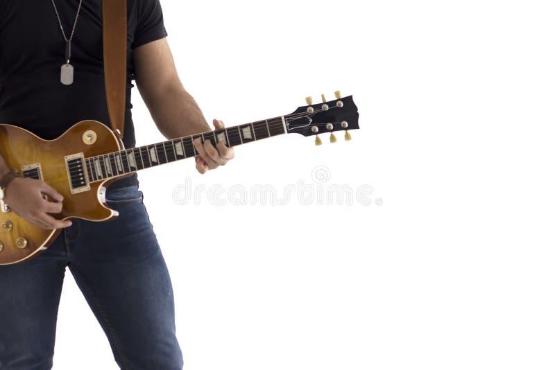 En man med en benägenhet för elektrisk gitarr mot en avkopplad cementvägg som är lycklig och vänta på showen royaltyfria foton