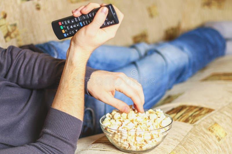 En man med en bunke av popcorn och en fjärrkontroll i hans hand ser TV:N på soffan arkivbilder