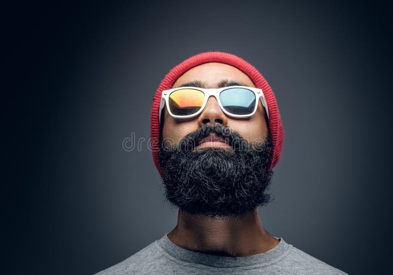 En man med det röda huvudet och färgrik ilsken blick i glasögon arkivbilder